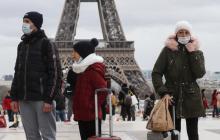 فرنسيون يرتدون أقنعة وجه أثناء سيرهم أمام برج إيفل في باريس (أرشيف)